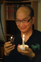 Jou compares his candlelight-like OLED (in right hand) with candle light. (Photo courtesy of Prof. Jou)