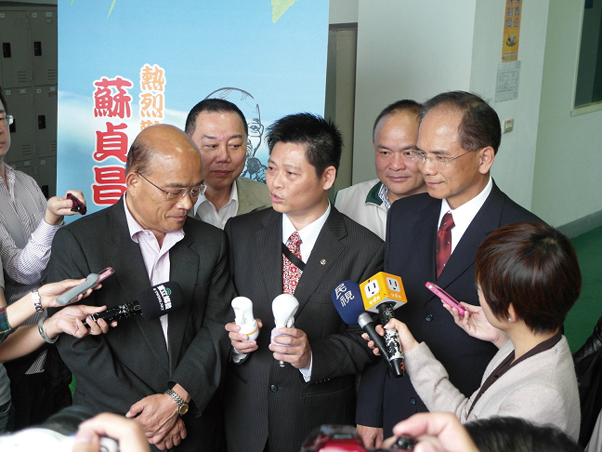 Chen (center) explains the characteristics of LVD induction lamps to former premiers Su Cheng-chang (left) and Yu Shyi-kun (right), as reporters watch.