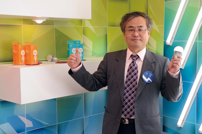 Bir-jen Wu holding an LED bulb from NYPI's automated line.