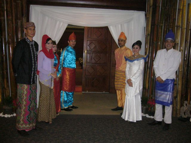 Receptionists in traditional Indonesian dress stand in front of the door, ready for the opening ceremony.