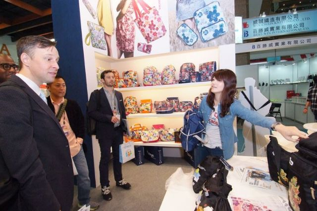 A booth showcasing various fashionable bags and knapsacks attracts foreign buyers.