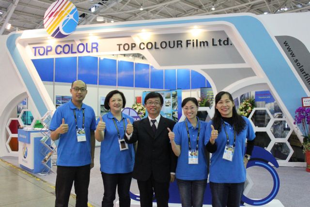 Top Colour president Robert Tsai, center, and his company staff pose in front of  his company's booth at 2014 Taipei AMPA.