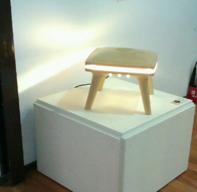 Seating and lighting functionality combine in this wooden stool by embedding a light source in the seat structure.
