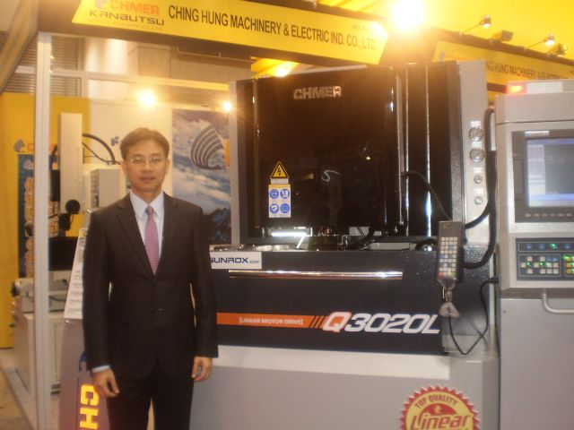 Brad Wang, Chmer's vice president, is proud of the technologies and key components built into his company's Q series high precision gantry-type liner motor drive EDM, seen behind him.