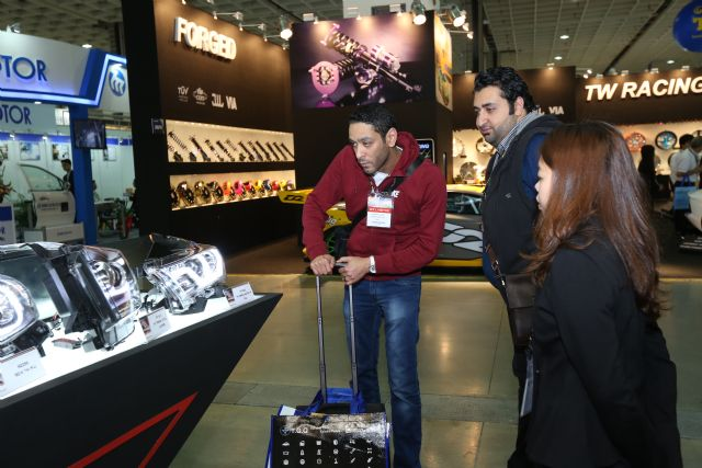 An exhibitor demonstrates a product to foreign buyers.