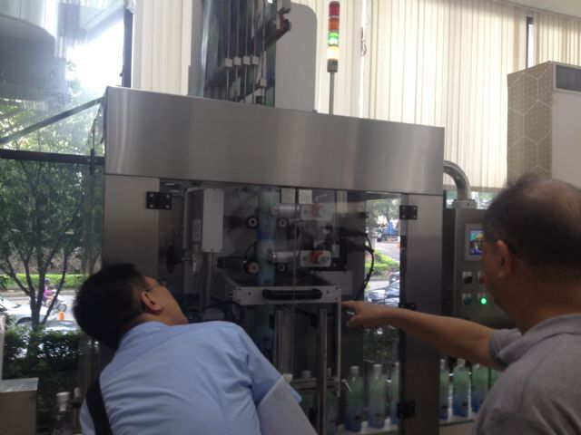 Visitors look at Benison's high-speed label sleeaving machine at the venue.