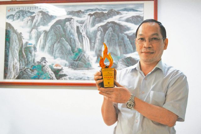 Y.C. Hu, chairman of Multiplas, shows the trophy for the firm's IMES IMS4.0 Smart Injection Molding System in Taipei Plas 2016 (photographed by Lu Siou-bin).