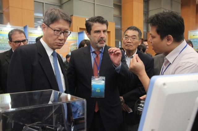 智慧穿戴式醫療眼鏡研發人員王民良(右白衣者),向新北市副市長葉惠青(左藍領)和巴西商務辦事處的主任Fábio Franco(中)等人介紹,Fábio充滿興趣。記者魏翊庭/攝影