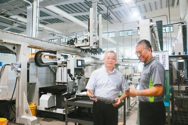 沈國榮(左)檢視大埔美園區新廠工業4.0智慧自動化產線開始試產情形。