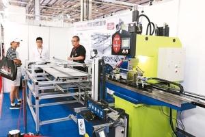 董事長劉芫誌(右)向客戶介紹薪瀝全自動精密油壓伺服器整直機台優異的加工性能。 黃奇鐘/攝影
