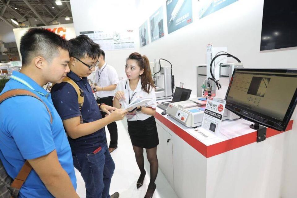 產品經理蔡易婷(右)向參觀來賓介紹多功能桌上型機械手「JTB Series」。東佑達/提供