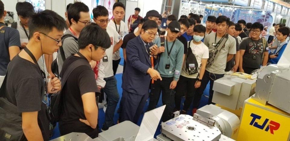 潭佳精密執行副總侯緯章(中著西裝者 )於台北國際工具機展中向來賓解說產品特性與功能。 潭佳精密/提供 潭佳精密/提供