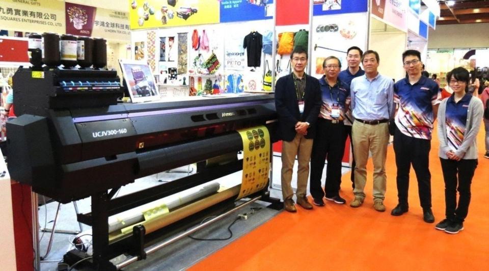 台灣御牧社長山田恭弘(前排左一)、總經理洪佑煥(前排左二)、副總有賀一普(前排左三)帶領專業團隊與UV捲料噴印機種UCJV300共同合影。業者/提供