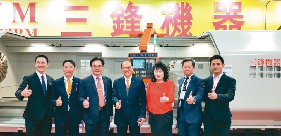 三鋒機器董事長林松益(左三)、總經理郭璦玫(左五)與來訪的上銀公司董事長卓永財(中)在TIMTOS展場合影。 魯修斌/攝影